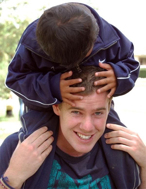 Projects Abroad vrijwilliger met Boliviaans kind op zijn nek