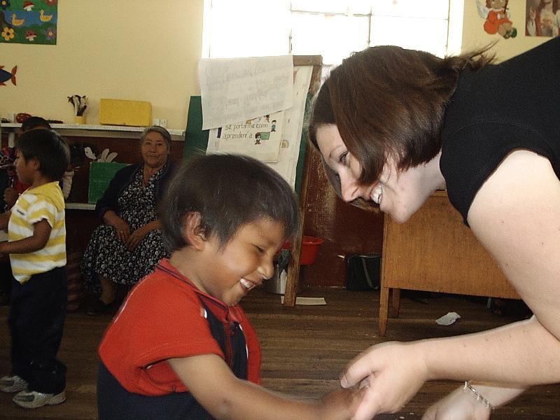 Projects Abroad vrijwilliger lacht met een Boliviaans kind op een sociaal project