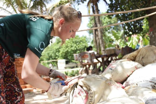 Vrijwilligers van de Anglia Girl Guides groep in Engeland helpen met het bouwen van faciliteiten bij een Cambodjaanse school op een sociaal project