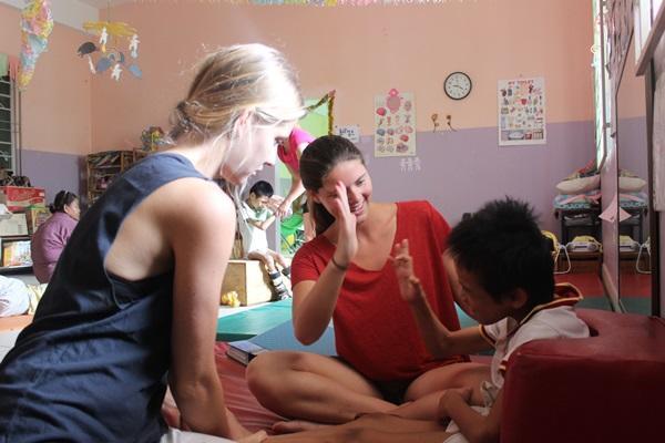 Vrijwilligers op het fysiotherapie project in Cambodja behandelen een jongen