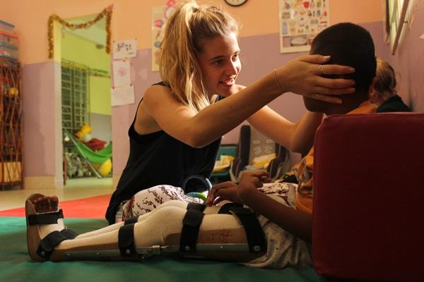 Vrijwilliger op het fysiotherapie project doet oefeningen met een patiënt in Cambodja