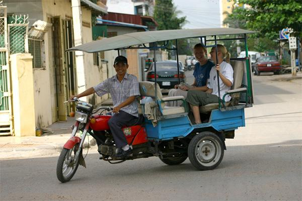 Twee Projects Abroad vrijwilligers in een typische tuktuk in Phnom Penh
