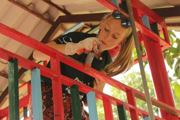 Vrijwilligers van de padvinderij in Engeland helpen met het verven van faciliteiten bij een Cambodjaanse school op een sociaal project