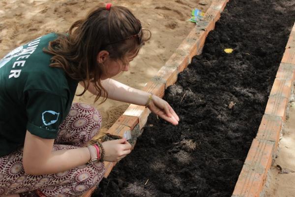 Vrijwilligers van de padvinderij in Engeland helpen met het zaaien van plantjes bij een Cambodjaanse school