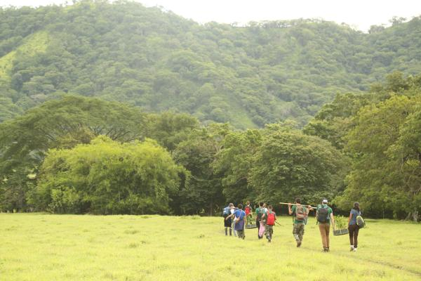 Vrijwilligers op weg naar herbebossing locaties rondom Barra Honda National Park met jonge boompjes en gereedschap