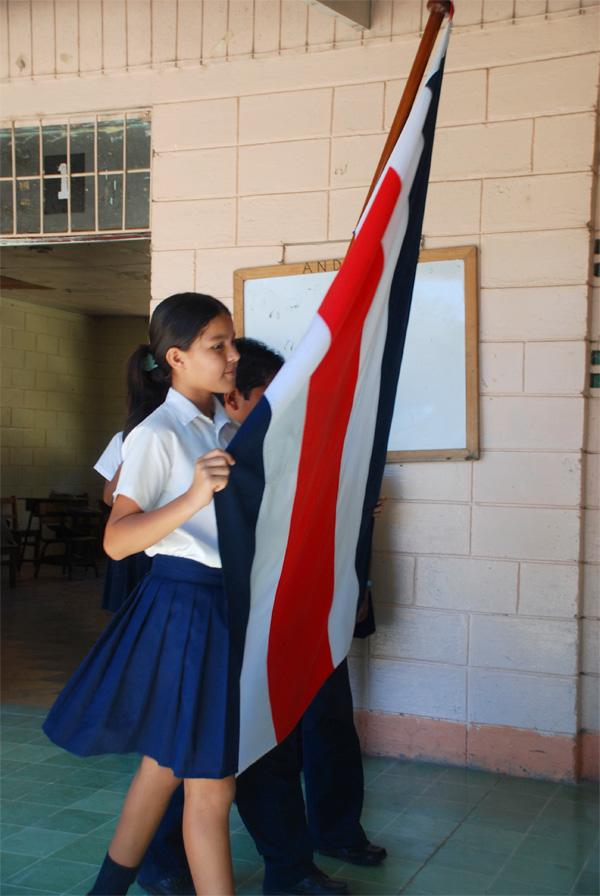 Schoolmeisje loopt met de nationale vlag van Costa Rica
