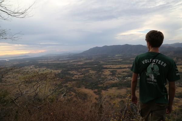Vrijwilliger op het natuurbehoud project kijkt over een vallei vanaf het uitkijkpunt, Mirador Nacaome, tijdens een vogelonderzoek in Barra Honda National Park