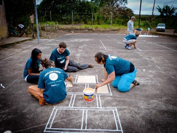 Vrijwilligers schilderen een hinkelbaan in Ecuador