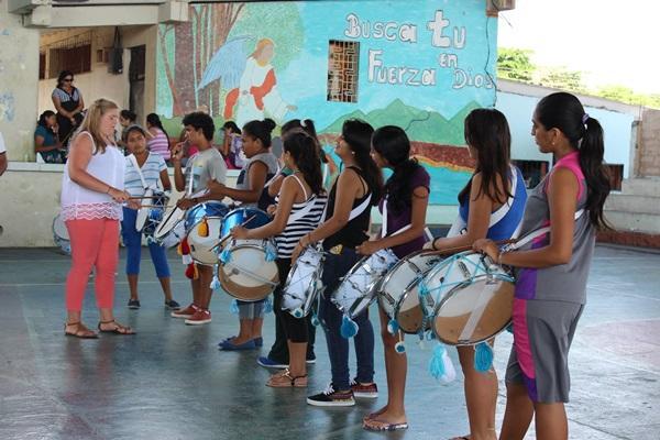 Kinderen maken muziek met trommels op het kunst & cultuur project in Ecuador