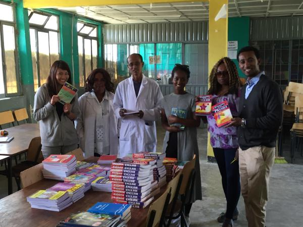 Projects Abroad medewerkers en vrijwilligers doneren boeken aan de directeur van de Berhane Zare School in Addis Ababa, Ethiopië