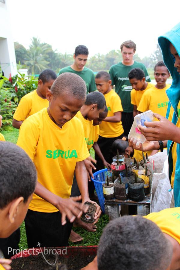 Kinderen van de Lomary Primary School helpen vrijwilligers met het herbeplanten van mangroven op het natuurbehoud project