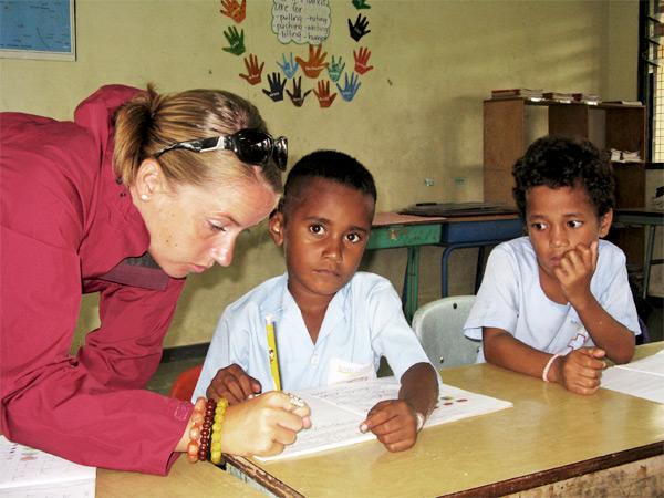 Projects Abroad vrijwilliger kijkt het werk na van een scholier in Fiji