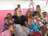 Een groepsfoto van een sociale zorg vrijwilligster en de kinderen tijdens verhaaltijd op een project in Fiji