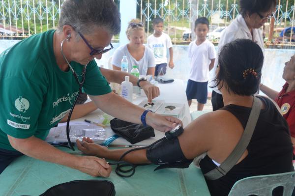 Vrijwilligers op het Public Health meet de bloeddruk tijdens een outreach in de Filippijnen