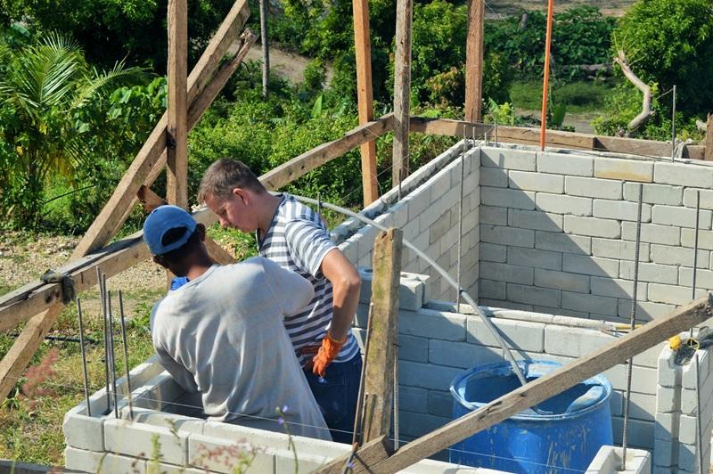 Vrijwilliger en lokale bouwvakker werken samen aan de wederopbouw in de Filippijnen