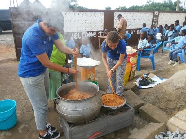 Projects Abroad vrijwilligers uit Zwitserland en Frankrijk koken joilog voor kinderen in een vluchtelingenkamp in Ghana