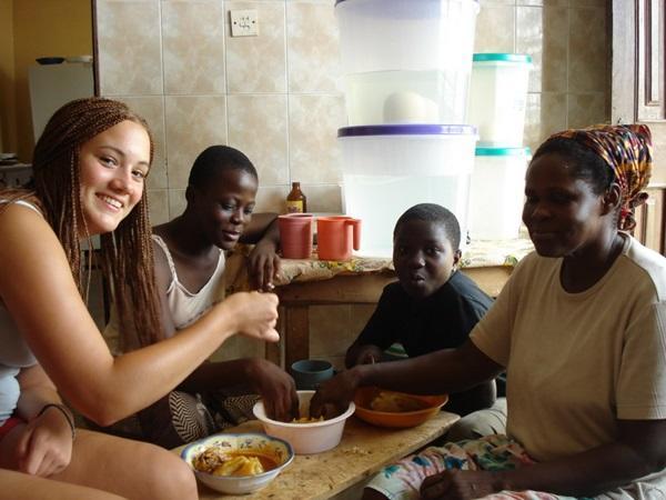 Vrijwilliger eet samen van de lokale lekkernijen met haar gastgezin in Ghana
