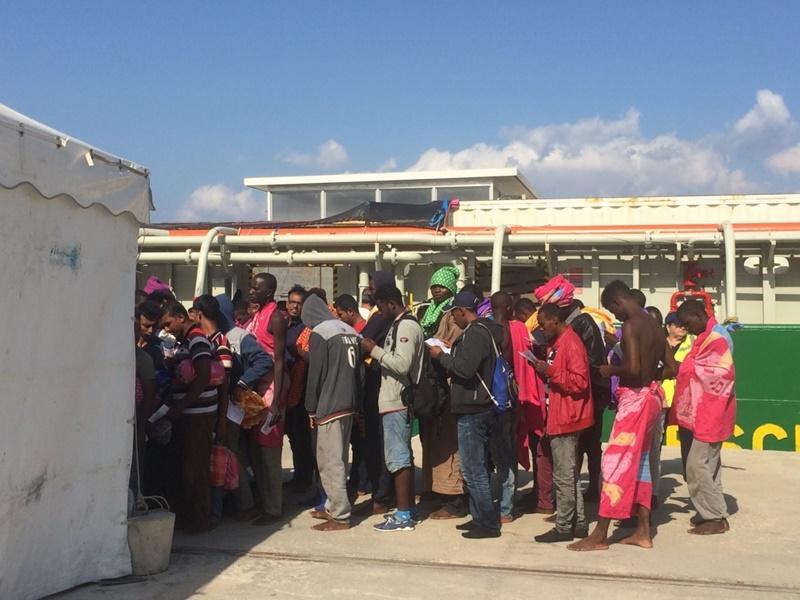 In Italië staan vluchtelingen in de rij met slechts enkele bezittingen