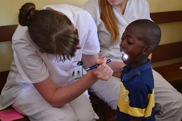 Projects Abroad medische vrijwilliger checkt het gebit van een jong kind tijdens een medische outreach in Jamaica