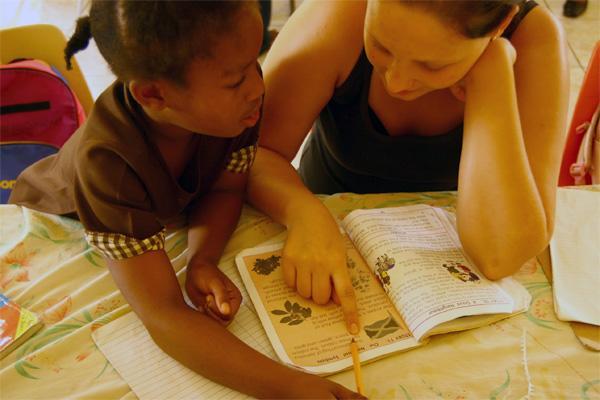 Projects Abroad vrijwilliger legt een verhaal uit op een lesgeef project op Jamaica