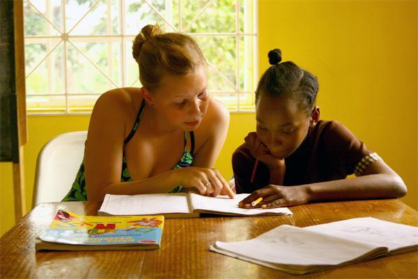 Projects Abroad vrijwilliger helpt scholier bij lesgeef project op Jamaica