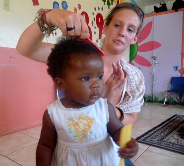 Projects Abroad vrijwilliger helpt meisje met het doen van haar haar op Jamaica