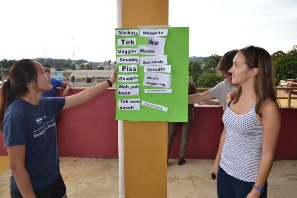 Een Amerikaanse en Canadese vrijwilliger leren woorden en uitspraak in het Patois tijdens een sociaal activiteit