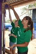Een groep vrijwilligers verven een schoolgebouw tijdens een community outreach