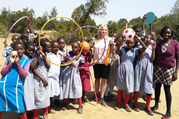 Een groep schoolkinderen poseert voor de foto met hoelahoepen op het sport project in Nanyuki, Kenia
