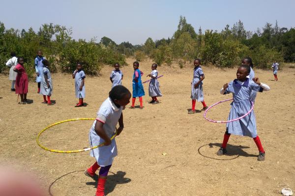 Schoolkinderen zijn aan het hoelahoepen tijdens een sportles op het sport project in Nanyuki, Kenia