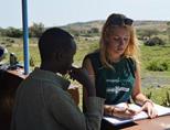 Een gezondheidzorgvrijwilliger schrijft gegevens op van een vrouw tijdens een medisch outreach in de buurt van Nanyuki, Kenia