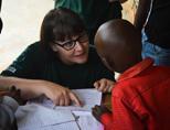 Een vrijwilliger helpt een klein kind met het maken van huiswerk tijdens een outreach in Kenia