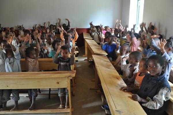 Schoolkinderen zwaaien naar de camera op het lesgeef project in Madagaskar