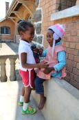 Twee lokale kinderen lachen met elkaar buiten hun huis in Madagaskar
