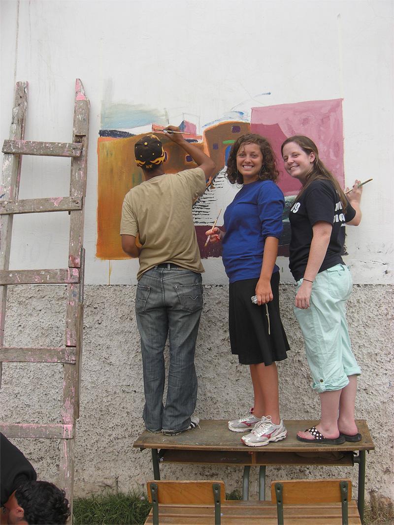Vrijwilligers van de jongerenreis maken een muurschildering