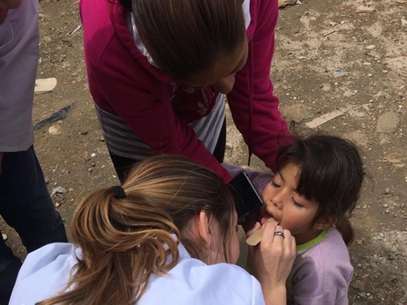 Projects Abroad vrijwilliger kijkt naar de keel van een kind op het Gezondheidszorg project in Mexico