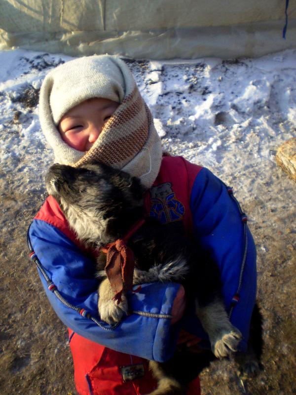 Nomadenkind speelt met hond in Mongolië