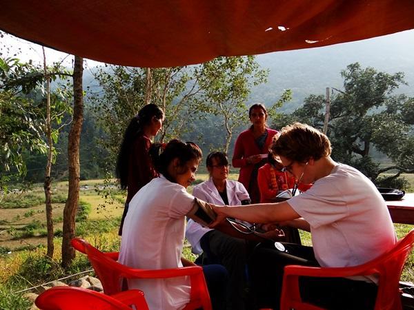 Een medische vrijwilliger controleert de bloeddruk van een jonge vrouw in Nepal