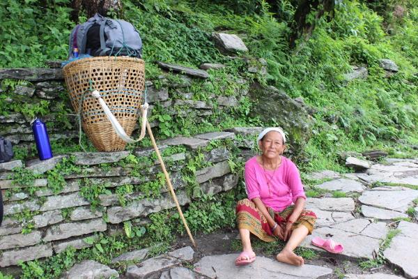 Een Nepalese vrouw lacht naar de camera terwijl ze aan de kant van de weg zit