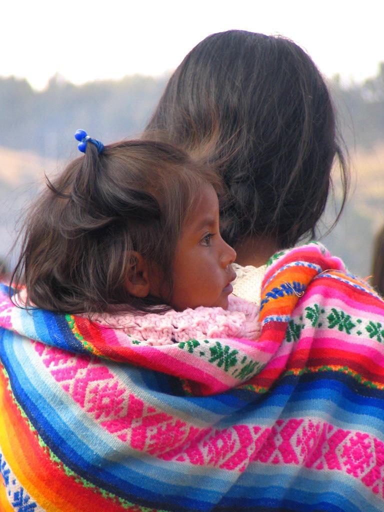 Peruaanse moeder draagt kind op haar rug