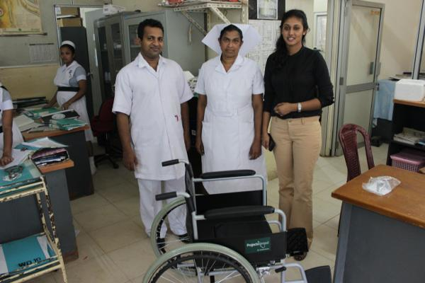 Projects Abroad medewerker en lokale medewerkers van het National Cancer Institute staan naast een rolstoel die gedoneerd is aan de medische afdeling