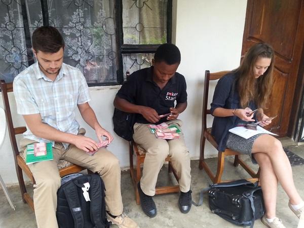 Vrijwilligers helpen met de boekhouding op het microkrediet project in Tanzania
