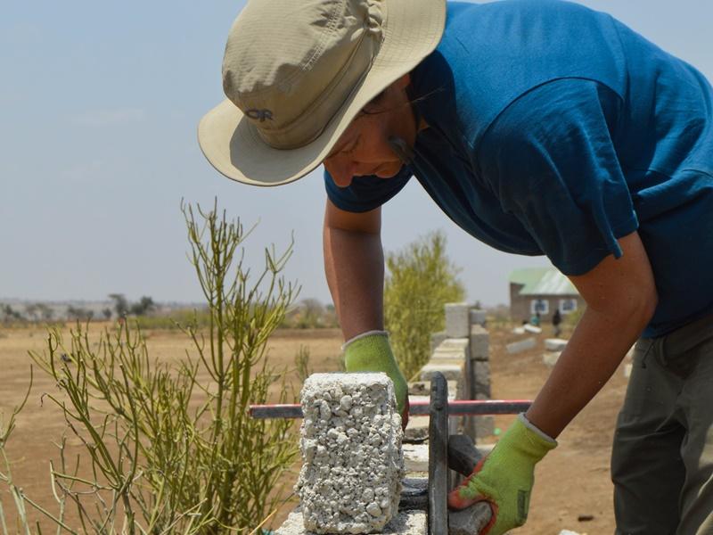 Een vrijwilliger helpt bij de bouw van een nieuwe school in Tanzania