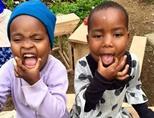 Lokale kinderen trekken gekke bekken op een Sociaal project in Tanzania