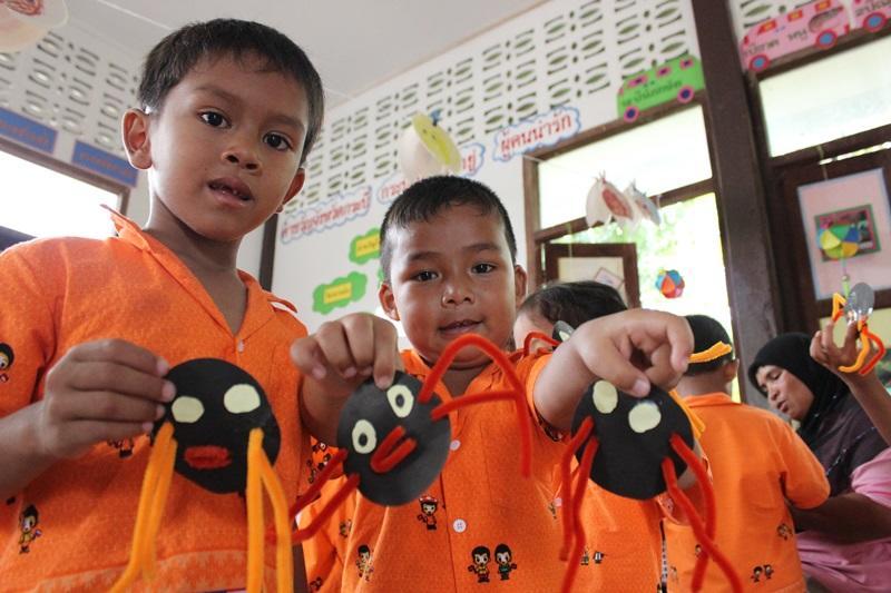 Vrijwilligers doen creatieve activiteiten met de kinderen op een sociaal project