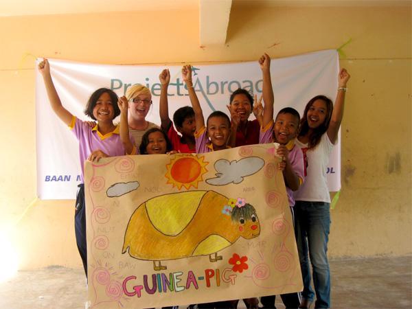 Projects Abroad vrijwilliger en kinderen laten knutselwerk zien