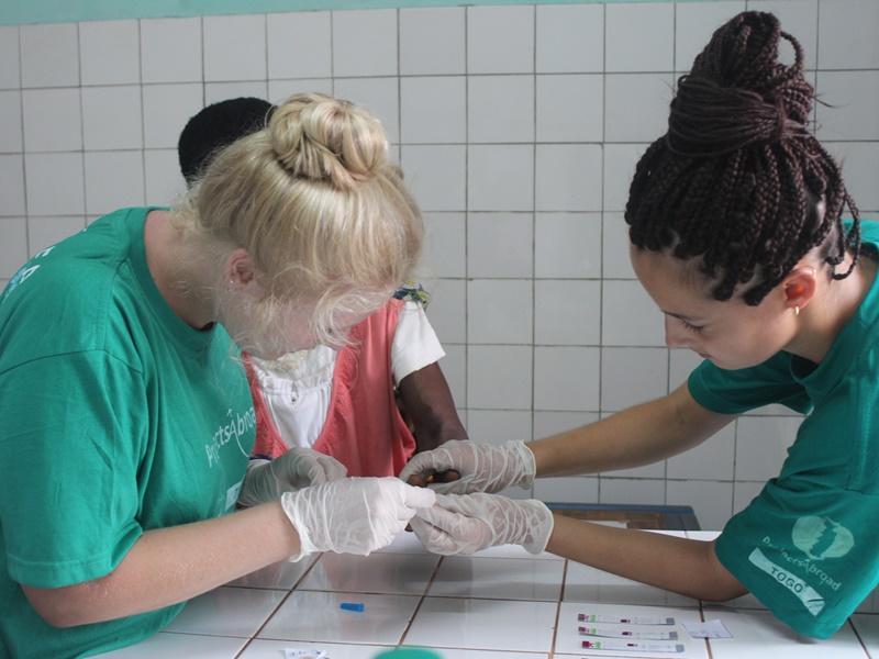 Een HIV-test wordt afgenomen door medische vrijwilligers in Togo