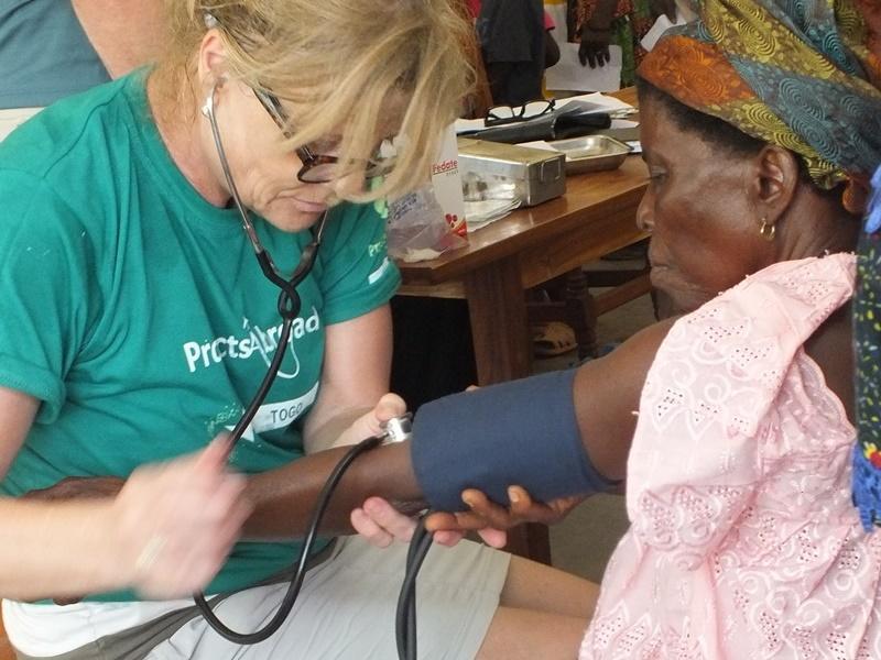 Vrijwilliger onderzoekt een vrouw tijdens een medische outreach