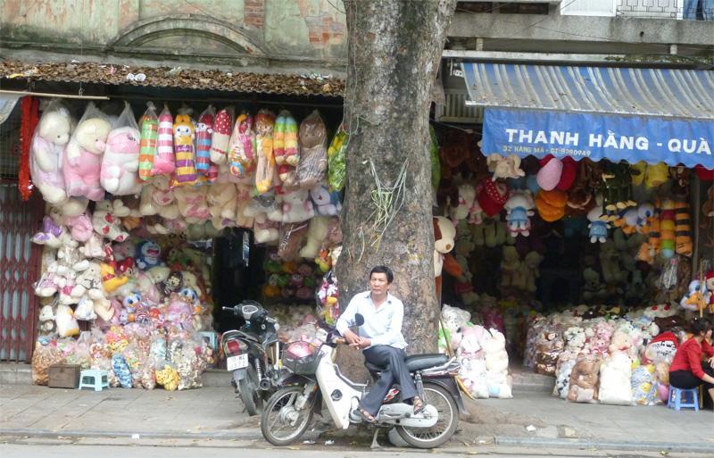 Een Vietnamese zakenman zit voor zijn marktstal in Hanoi