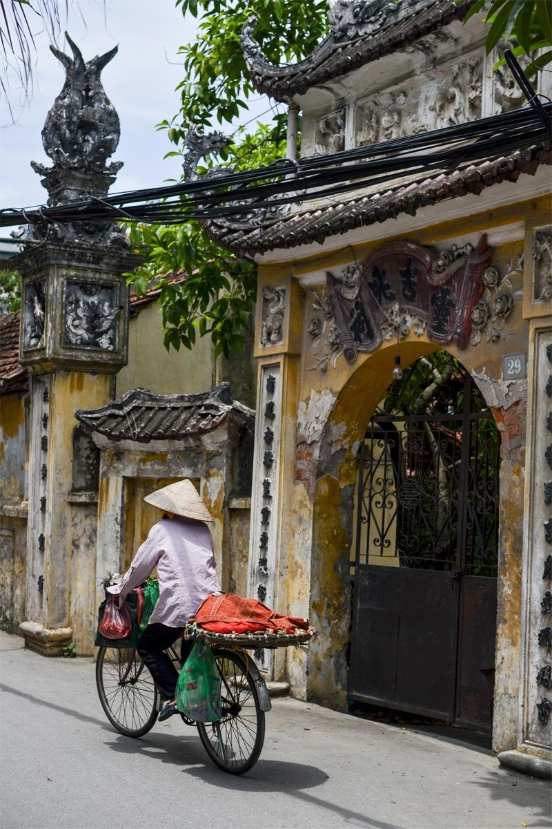 Een vrouw met een traditionele Vietnamese hoed fietst langs een oude tempel
